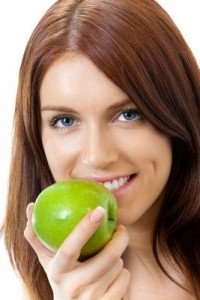 zufriedener Patient mit grünem Apfel in der Zahnklinik Ungarn